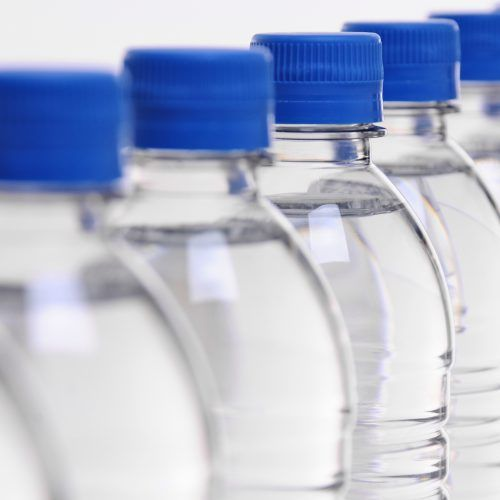 select focus on middle bottle in a row of water bottles