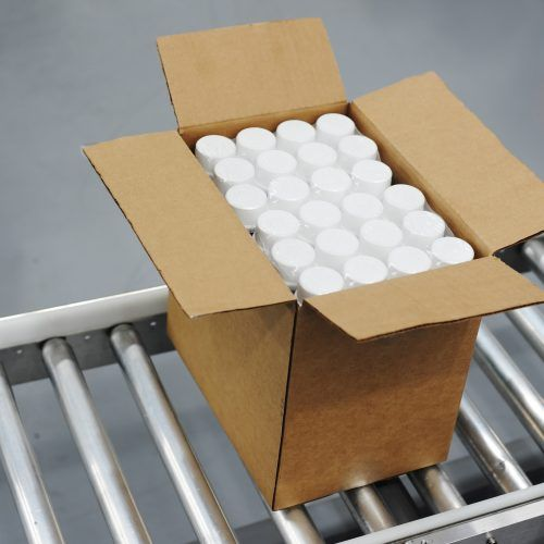Shot of single, unsealed box traveling on a conveyor in a manufacturing facility. Plastic bottles are visible inside the box.